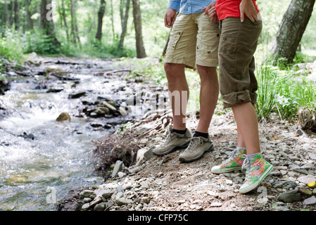 Couple hiking along stream in woods, low section - Stock Photo
