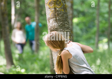 Girl hiking behind tree in woods - Stock Photo