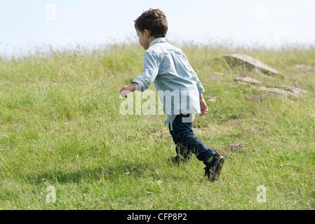 Little boy running in meadow, rear view - Stock Photo