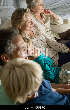 Multi-generation family sitting side by side on sofa, high angle view - Stock Photo