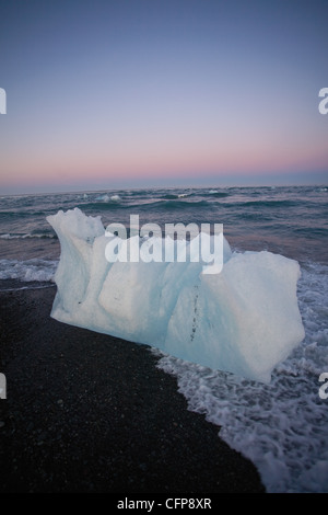 Large piece of glacial ice washed up on beach, Jokulsarlon glacial lagoon, Iceland - Stock Photo