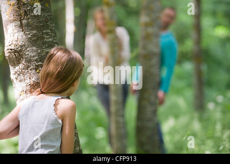 Girl playing hide and seek with parents in woods, rear view - Stock Photo