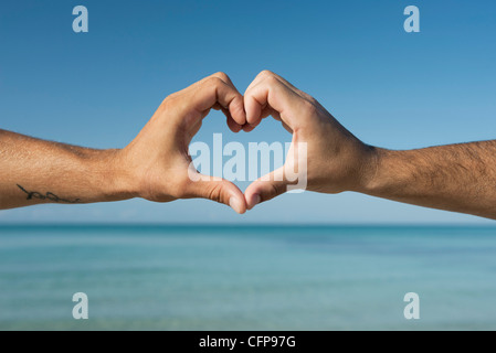 Two men's hands forming heart shape by ocean, cropped - Stock Photo