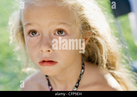 Little girl looking up anxiously, portrait - Stock Photo