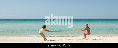 Children playing tug-of-war with bamboo at the beach - Stock Photo