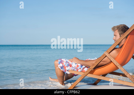 Young man reclining in deckchair looking at ocean, side view - Stock Photo