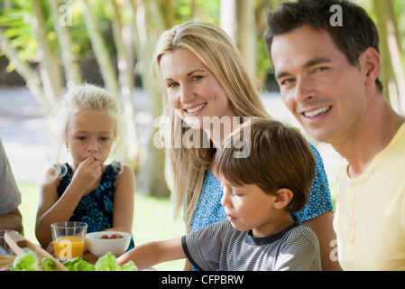 Family having meal outdoors, focus on young woman - Stock Photo
