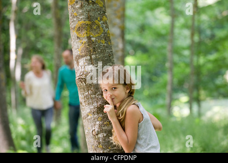 Girl hiding behind tree with finger on lips - Stock Photo