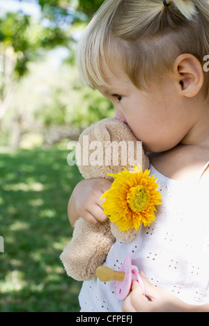 Little girl holding teddy bear, flower and pacifier - Stock Photo