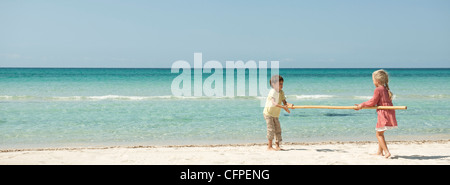 Children carrying bamboo together at the beach - Stock Photo