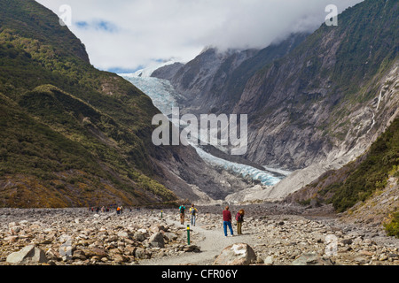 Tourists approaching the terminal of Franz Josef Glacier, West Coast, New Zealand - Stock Photo