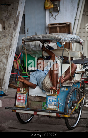 Driver sleeping in his taxi rickshaw (tricycle) in Makassar, Sulawesi, Java, Bali, South Pacific, Indonesia Southeast - Stock Photo