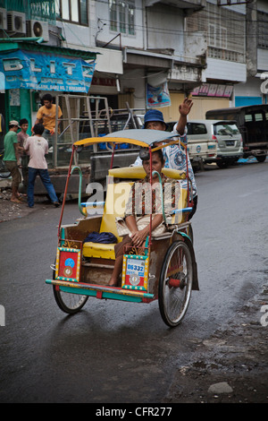 Taxi rickshaw (tricycle) in a street of Makassar (Ujung Pandang), Sulawesi, Indonesia, South Pacific, Asia. - Stock Photo