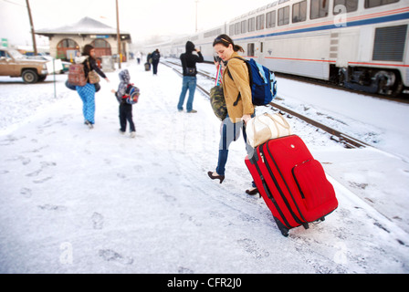 Woman pulling luggage through snow after deboarding an Amtrak train in Oregon - Stock Photo
