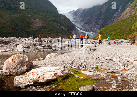 Tourists crossing a bridge near Franz Josef Glacier, West Coast, New Zealand. - Stock Photo