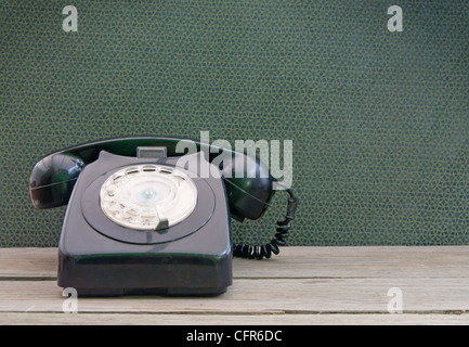 Vintage phone on a wooden table with wallpaper in the background - Stock Photo