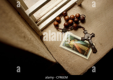 Wooden rosary and Jesus image at window sill. - Stock Photo