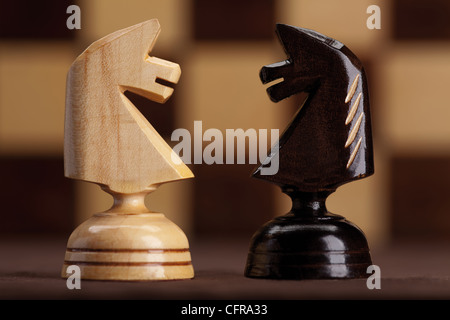 white and black knights on chessboard background - Stock Photo