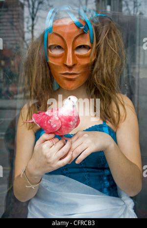 Girl in mask holding pink dove, Belfast City Center. - Stock Photo
