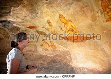 Femaile tourist looks at Apsara frescoes at Sigiriya Rock, UNESCO World Heritage Site, Sri Lanka, Asia - Stock Photo