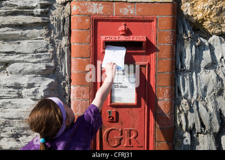Little girl posting postcards into a red postbox in Woolacombe, Devon - Stock Photo