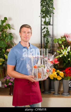 Male Florist in flower shop or nursery presenting his plants on display - Stock Photo