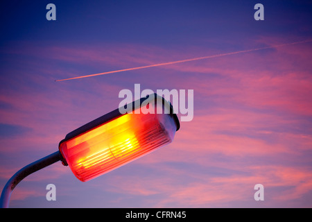 plane contrail at sunset near Windermere UK with a street lamp. - Stock Photo