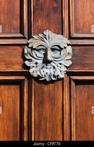 Green Man doorknocker on a wooden door. - Stock Photo