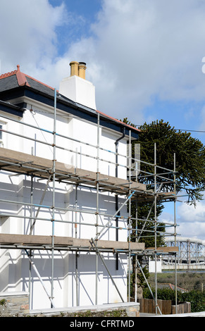 Scaffolding around a house undergoing some repairs - Stock Photo