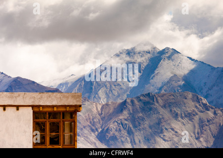 A typical Ladakhi house with tall misty mountains in the background. - Stock Photo