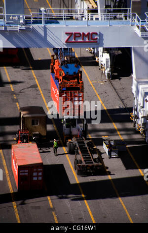 Gang longshoremen direct an overhead crane transferring maritime cargo containers from a ship's hold to truck transportation - Stock Photo