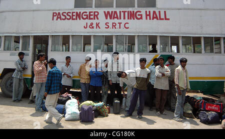 Non Kashmiri Labourers waiting alongside their luggage at a bus terminal in Srinagar, summer capital of indian administered - Stock Photo