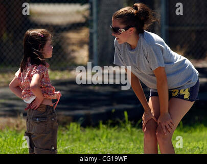 Counselor Cassie Cooper, right, stops to talk with a young camper as they play a game at Quest Camp in Alamo, Calif., - Stock Photo