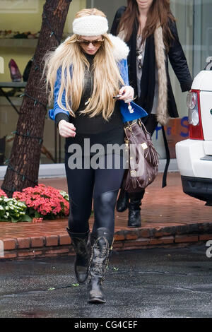 Lindsay Lohan goes for some retail therapy at Fred Segal on Melrose Avenue with a friend on a rainy day.  Los Angeles, - Stock Photo