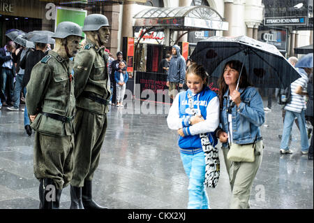 Nazi Zombies stand in the rain as people walk past with umbrellas in Leicester Square. The Zombies were attending - Stock Photo