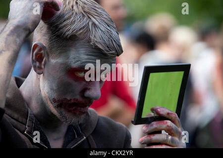 A Zombie at Stockholm Zombie Walk 2012. A guy putting the finishing touches on his zombie makeup. - Stock Photo