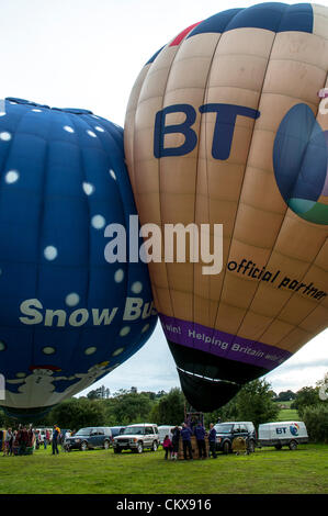 26th Aug 2012. Dave Baker G-ZOIZ M-Type (M-105) BT LONDON 2012 balloon and the G-SBIZ Cameron Z.90 Snow Business Hot Air Free Balloon bump together as they prepare for launch at the Tiverton balloon festival in Tiverton, Devon, UK.
