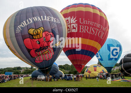 26th Aug 2012. The G-POLY, 1978 CAMERON N-77 Pollywallets ballon Cameron-Z Series (UK) (Gottex) (Z-90) (G-CCNN) balloon and the John Harris (G-CDWD)  University of Bristol balloon is prepared for launch at the Tiverton balloon festival in Tiverton, Devon, UK.