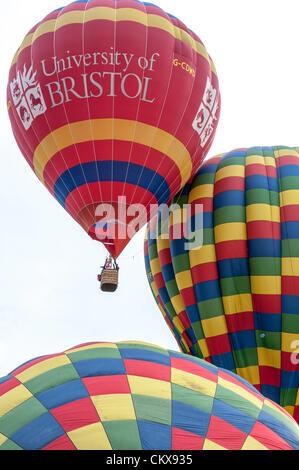 26th Aug 2012. The John Harris (G-CDWD) University of Bristol balloon takes off beside the Colin Hodges G-CFFL Lindstrand LBL-317A Aerosaurus balloon at the Tiverton balloon festival in Tiverton, Devon, UK.