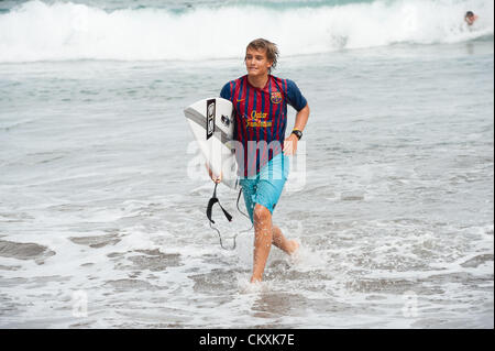 LAS PALMAS, CANARIAS ISLANDS, SPAIN–AUGUST 29, 2012: Unidentified young surfers from University Surf School and - Stock Photo