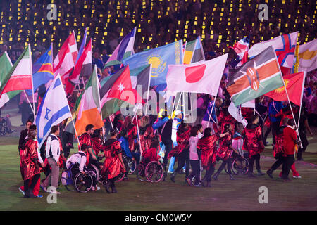 Athletes carry their countries' flags into Olympic Stadium at the closing ceremony of the 2012 Paralympic Games - Stock Photo