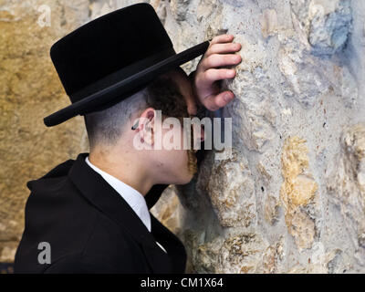 A man buries his head in the stones of the Western Wall as he prays on the Eve of the Jewish New Year, Rosh Hashanah. - Stock Photo