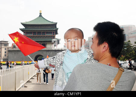Xian, China. Saturday 15th September, 2012. A young father with his little son holding a Chinese national flag walks - Stock Photo