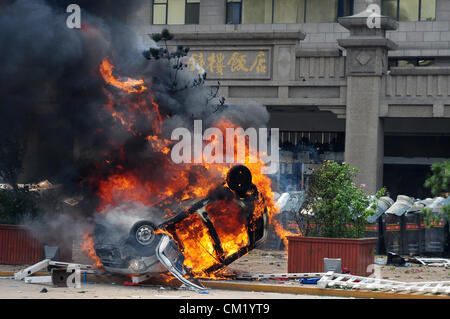 Xian, China. Saturday 15th September, 2012. Anti-Japanese protesters burn a car during a demonstration at Bell Tower - Stock Photo