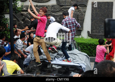 Xian, China. Saturday 15th September, 2012. Anti-Japanese protesters damage and break a Japanese brand car during - Stock Photo