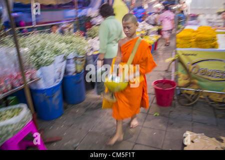 Oct. 9, 2012 - Bangkok, Thailand - A novice Buddhist monk walks through the Bangkok Flower Market. Most males in - Stock Photo