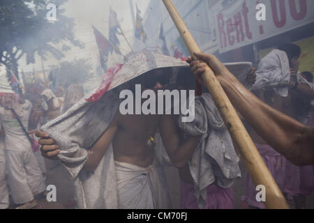Oct. 19, 2012 - Phuket, Thailand - A man shields himself from exploding fireworks during a street procession at - Stock Photo