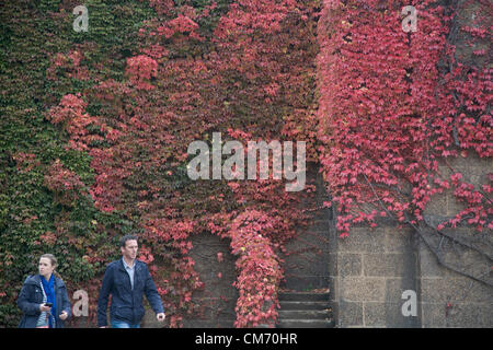 London, UK. 19th October 2012. People walk past Autumn display of colors on Horse Guards Parade in London. Credit: - Stock Photo