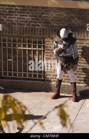 New York, USA. October 22nd 2012. O Positive Films. An actor dressed as an Alien uses a smart phone while on a break - Stock Photo