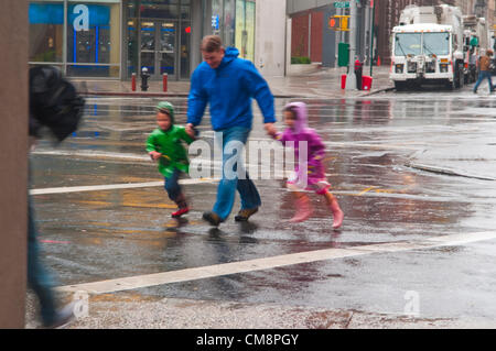 New York, NY -  29 Oct 2012 A father with two small children rush across East 8th Street, in the East Village, during - Stock Photo